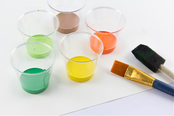 Paint in plastic tubs with a paintbrush and paper to make a handprint Earth Day craft with kids
